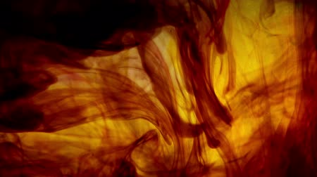 espalhando : Colored ink dropped into water. Tobacco color.  Stock Footage