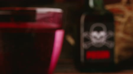 clínico : Poison, red glass in front, shallow depth of field