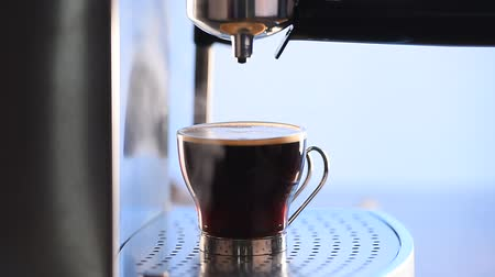 gourmet : Modern glass cup of black coffee brewing via a metal espresso machine, hd, 1080p high definition.