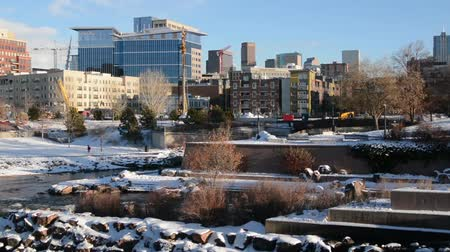 creek : City skyline pan, Denver downtown seen from Confluence Park, Jogger in distance