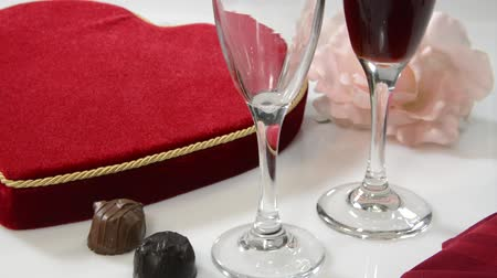 kırmızı şarap : Burgundy wine being poured with a heart shaped box of chocolates in background