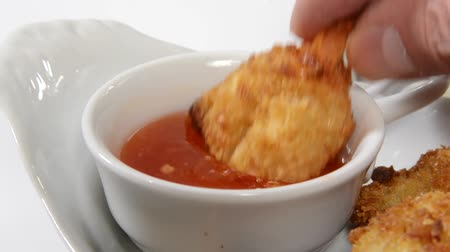 alkol : Coconut shrimp being dipped in sweet sauce