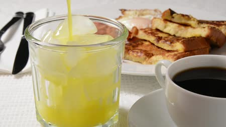 küpleri : Pouring orange juice into a glass with french toast and coffee in background