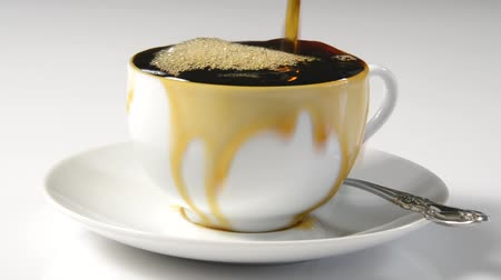 xícara de café : Coffee pouring into a cup and overflowing indicating absent mindedness