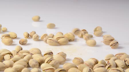 nasiona : Pistachios pouring onto a white counter top