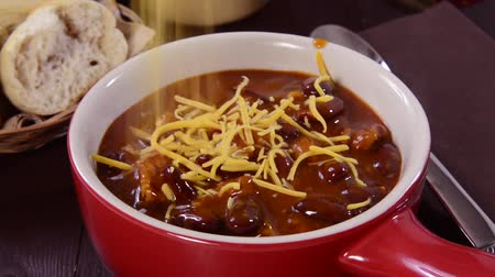 chili : Sprinkling cheddar cheese on a bowl of chili