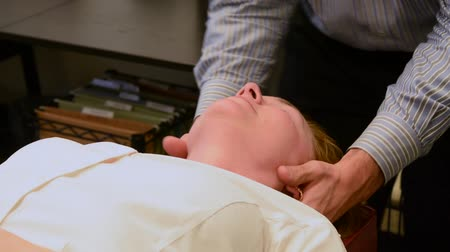 healthy office : A woman receiving a neck adjustment in a chiropractic office
