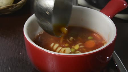 kufel : Ladling vegetable soup into a stoneware mug