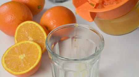 Pouring fresh squeezed orange juice into a glass Vídeos