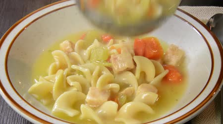 Ladling chicken noodle soup into a bowl