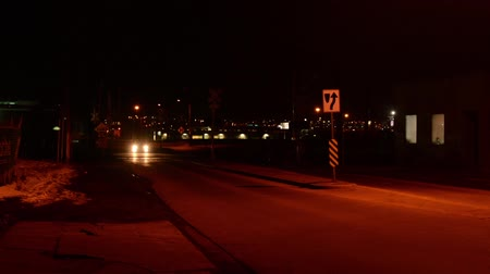 Cars at a train crossing at night