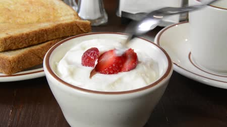 feketés csésze : Eating a spoonful of yogurt with strawberries