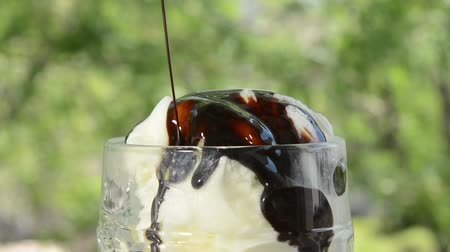 pouring chocolate syrup on ice cream outdoors Vídeos