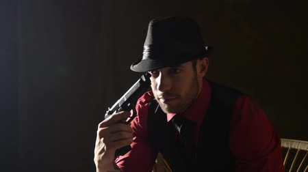 mroczne : A man in a dark room tipping his hat with a gun