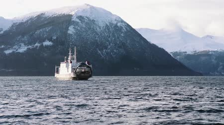 Ferry on the fjord with snow mountains, near volda (norway) Stock mozgókép