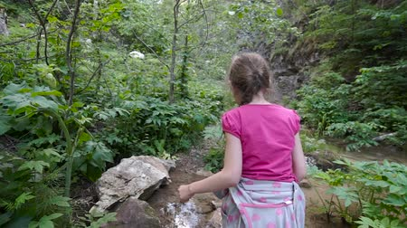 Young girl goes on mountain trail.