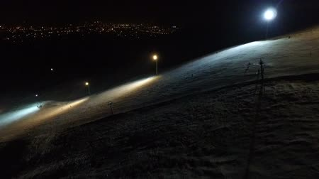 hegyoldalban : Ski resort slope on the night city background. Stock mozgókép