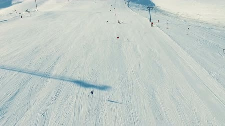 холм : Several people ride ski by snow slope, view from ropeway in motion