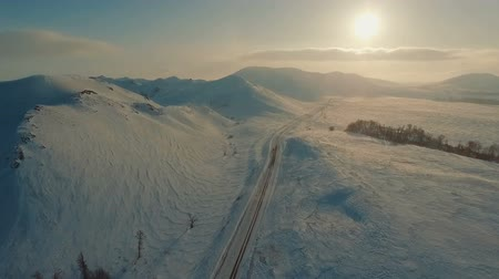 snowcapped : Several cars driving on icy road at the dusk near the mountains. Stock Footage
