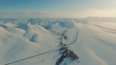 wschód słońca : Winter in the mountains. Flying over the road in winter. Wideo