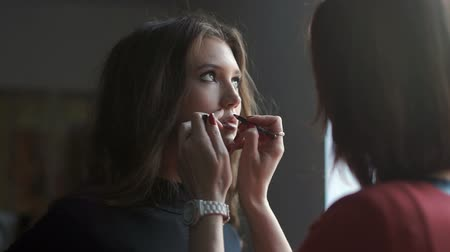 румяна : Specialist doing makeup for model. Gentle make-up for the young girl.
