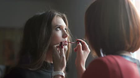 rouge : Make up artist doing makeup for model. Lip gloss application