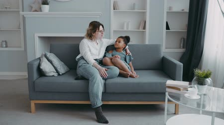 puericultura : Beautiful young caring mother wearing shirt on sofa talking smart pretty african american daughter with curly black hair in blue dress, mum enjoying hugging spending time with little funny kid at home Stock Footage