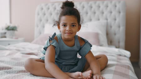 Portrait of pretty happy smiling looking at camera at home cute afro american girl, child with curly hair sits on bed in cozy bedroom wear blue chintz dress joyful kid daughter multinational family