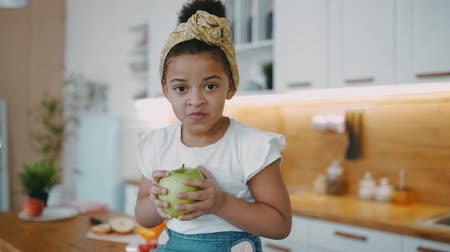 honger : Pretty little african american girl with curly hair sits on table with green fresh apple in her hands, light sunny kitchen in cozy apartment smiling looking at camera wearing white T-shirt and headband