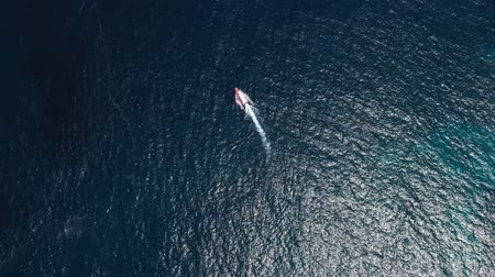 крейсер : Top view from above boat anchored yacht floating in ocean runabout or cruiser stands in azure sea waters with coral reef visible. Weekender from drone beautiful weather with calm sea and sun shining