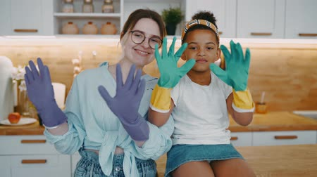 dezenfekte etmek : Mother in glasses and daughter african american girl wearing rubber gloves to clean kitchen wash dishes to protect hands from household chemicals, woman and child in playful mood engage daily routine