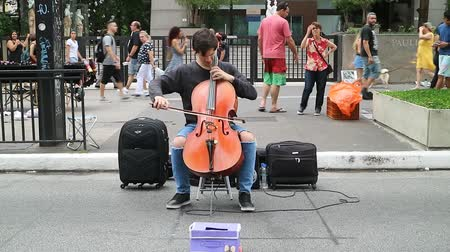 виолончель : Sao Paulo, Brazil – November 11, 2018: Unidentified musician playing classical sound with cello on Avenida Paulista. On Sundays, the avenue is generally open to citizens and street performers.