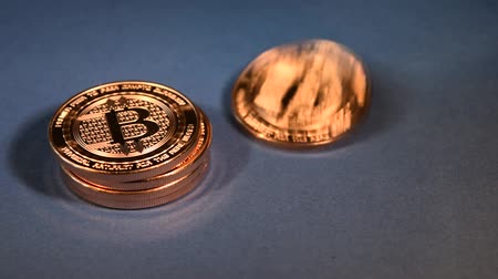 Stack of Bitcoins, One Coin Toppling, Blue Background