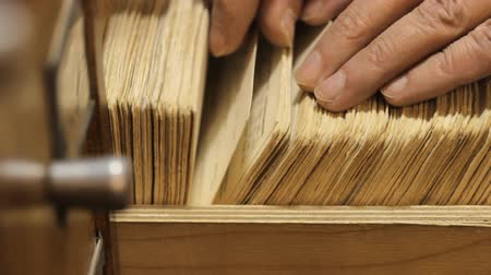 drawer : man searches something in card catalog