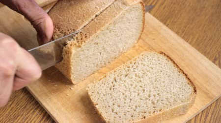 Hands slice loaves of bread