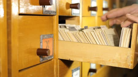 Man looking for a book in the library card catalog Vídeos