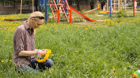 Mother weaves a wreath of dandelions for her daughter