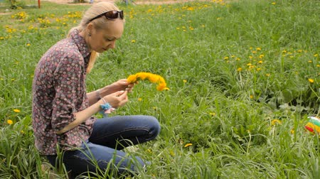 A woman weaves a wreath of dandelions Vídeos