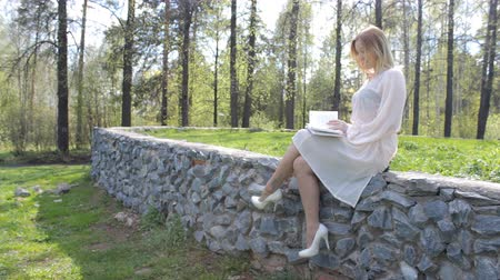 Girl sits on a bench with a book