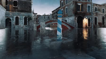 Empty venetian street with flooded sidewalks, ancient buildings and old bridge over water canal during anomalous flood Acqua Alta in Venice at rainy day