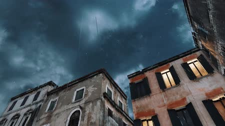 Looking up at ancient buildings against dull stormy sky with dark clouds at heavy rain during flood Acqua Alta in Venice, Italy. Bad weather concept realistic 3D animation. Dostupné videozáznamy