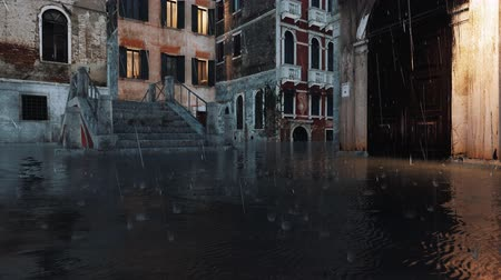 Flooded with water pavement and ancient bridge on empty venetian street during flood Acqua Alta in Venice, Italy at evening with heavy rain