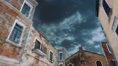 Looking up at ancient historic buildings against stormy sky background at heavy rain during flood Acqua Alta in Venice, Italy