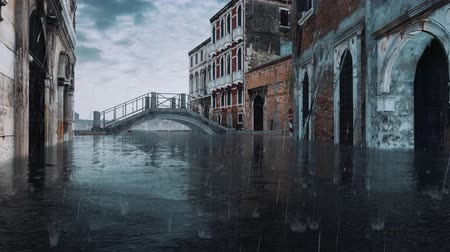 submerso : Narrow venetian street with flooded ancient buildings and old stone bridge during catastrophic flood Acqua Alta in Venice at dusk with heavy rain