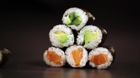 прокатка : Maki sushi rolls rolling and forming a triangle on black backround.