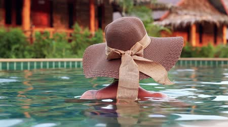 sunhat : Young Woman With hat From Back In Swimming Pool in exotic luxurious resort.