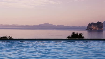Luxurious Infinity swimming pool at sunset on tropical island, Andaman sea in background. Thailand, asia, Stok Video