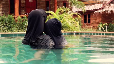 Muslim child hugging mother with hijab in swimming pool on vacation.