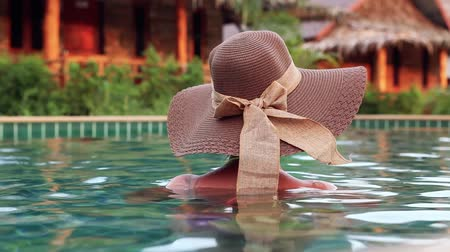 sunhat : Sexy Woman With Sunhat From Back In Swimming Pool in exotic luxurious resort in Krabi, Thailand, Asia. Stock Footage
