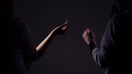 addicted : Passing marijuana cigarette in dark empty room between two people. Stock Footage